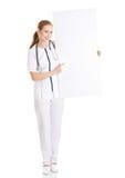 拿着空的白板的美丽的白种人护士或医生。 库存图片