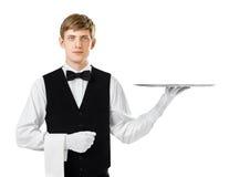 拿着空的盘子的年轻英俊的侍者 免版税库存照片