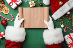 拿着空的纸卷和圣诞节装饰在颜色背景,顶视图的圣诞老人 库存照片