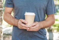 拿着空的纸咖啡杯的人 模板嘲笑 库存图片