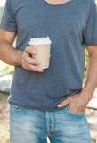 拿着空的纸咖啡杯的人 模板嘲笑 免版税库存照片