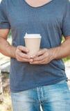 拿着空的纸咖啡杯的人 模板嘲笑 图库摄影