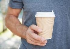 拿着空的纸咖啡杯的人 模板嘲笑 库存照片