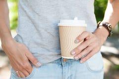 拿着空的纸咖啡杯的妇女 模板嘲笑 免版税库存照片