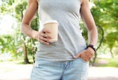 拿着空的纸咖啡杯的妇女 模板嘲笑 免版税库存图片