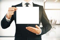 拿着空的纸板料的商人 免版税库存照片