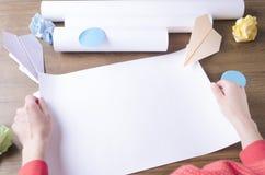 拿着空的纸,压皱纸,纸飞机的妇女作为起动的标志 做计划的概念起动 免版税库存照片