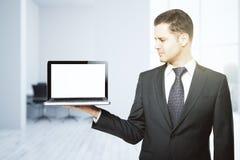 拿着空的膝上型计算机的人 免版税库存照片
