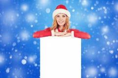 拿着空的董事会的圣诞老人帽子的圣诞节妇女 免版税库存照片