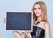 拿着空的黑板的少妇 免版税库存照片