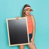 拿着空的黑板的微笑的女孩 免版税库存照片
