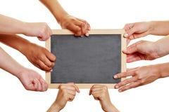 拿着空的黑板的许多学生 库存照片