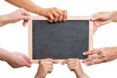 拿着空的黑板的许多手 免版税库存图片