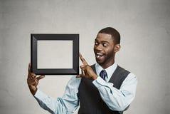 拿着空的画框的愉快的商人 库存照片