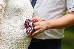 拿着童鞋的一名孕妇和她的丈夫的特写镜头 免版税图库摄影