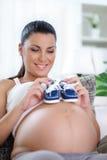 拿着童鞋的孕妇 图库摄影