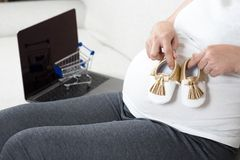拿着童鞋的愉快的孕妇手,当坐gr时 库存图片