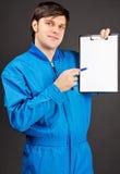 拿着笔和一张空白剪贴板的年轻工人纵向 免版税库存图片