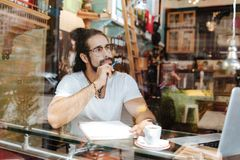 拿着笔的英俊的有胡子的人 免版税库存照片