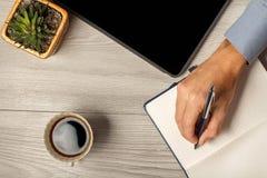 拿着笔的Man's手准备好采取在笔记本的笔记 免版税库存图片