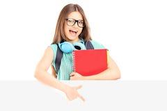 拿着笔记本和指向在盘区的激动的女学生 免版税库存图片