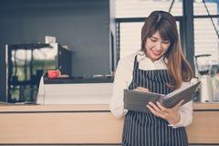 拿着笔记本的小企业主在咖啡店的柜台 图库摄影