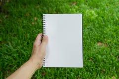 拿着笔记本的手 库存照片