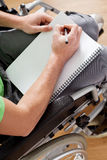 拿着笔记本的残疾人 免版税库存图片