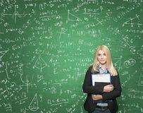拿着笔记本,有标志的绿色黑板的女孩在Th 免版税图库摄影