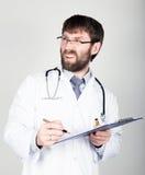 拿着笔记的,听诊器的医生的特写镜头portret地图情形在他的脖子上 不满看的他 免版税库存图片