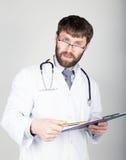 拿着笔记的,听诊器的医生的特写镜头portret地图情形在他的脖子上 他凝视照相机 免版税库存照片