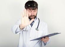 拿着笔记的,听诊器的医生的特写镜头portret地图情形在他的脖子上 他今后举起了他的手,棕榈 免版税库存图片
