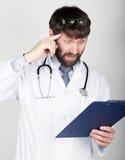 拿着笔记的,听诊器的医生的特写镜头portret地图情形在他的脖子上 他扭转他的食指在他的 免版税库存图片