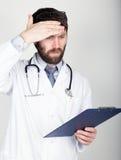 拿着笔记的,听诊器的医生的特写镜头portret地图情形在他的脖子上 他抹他的前额 不同 图库摄影