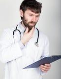 拿着笔记的,听诊器的医生的特写镜头portret地图情形在他的脖子上 他摩擦他的下巴 不同 库存图片
