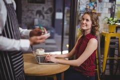 拿着笔记薄的侍者的中央部位,当支持微笑的年轻女性顾客时 库存图片