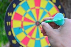 拿着箭的手准备好瞄准掷镖的圆靶 免版税库存照片
