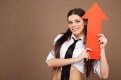 拿着箭头标志的女小学生服装的妇女 库存照片