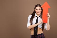 拿着箭头标志的女小学生服装的妇女 图库摄影