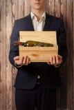 拿着箱子用酒的典雅的人反对木背景 免版税图库摄影