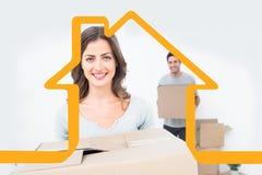 拿着箱子的俏丽的妇女的综合图象在她的新房里 免版税库存照片