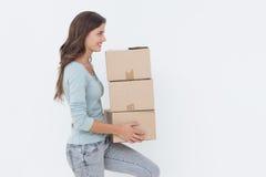 拿着箱子的妇女,因为她在一个新房里移动 库存照片