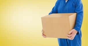 拿着箱子的送货人反对黄色背景 免版税图库摄影