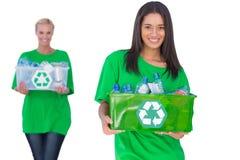 拿着箱子recyclables的两名enivromental活动家 免版税图库摄影