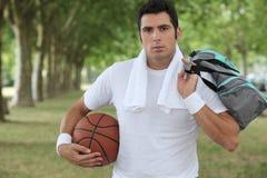 拿着篮子球的人 库存图片