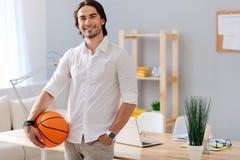 拿着篮子球的快乐的英俊的人 库存照片