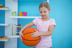 拿着篮子球的逗人喜爱的女孩 免版税库存照片