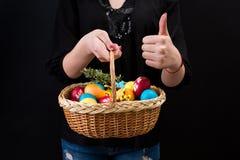 拿着篮子用五颜六色的复活节彩蛋和显示赞许的妇女 拿着在黑背景的手复活节篮子 库存图片