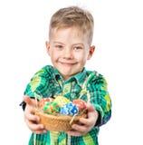拿着篮子用复活节彩蛋的愉快的男孩 查出在白色 图库摄影