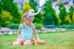拿着篮子用复活节彩蛋的可爱的小女孩佩带的兔宝宝耳朵 免版税库存照片